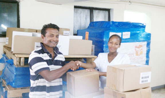 Sharir Chan, Chief Operations Officer, Guyana Medical Re-lief presents boxes of medication and supplies to a representative of the Mahaicony Hospital.