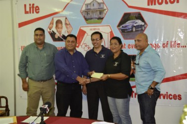 Hand-in-Hand, Human Resources and Administrative Manager, Zaida Joaquin (second right) hands over the cheque to president of the DCB, Raj Singh in the presence of other DCB officials and Director and Fire Manager of the insurance company, Howard Cox.