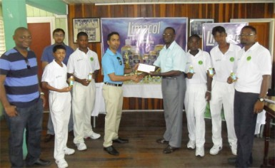 Guyana Cricket Board's Competitions Committee Chairman Colin Europe (5thfrom right), accepts the sponsorship cheque from New GPC Inc. Marketing Manager Trevor Bassoo, while other GCB and New GPC Inc. executives and players look on.