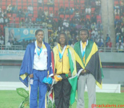 Jevina Straker (center) stands on the podium with her gold medal following her win in the girls' U20 1500m final in The Bahamas at the Thomas Robinson Stadium.