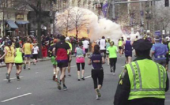 Runners continue to run towards the finish line of the Boston Marathon as an explosion erupts near the finish line of the race in Boston, Massachusetts, April 15, 2013. (Reuters/Dan Lampariello)