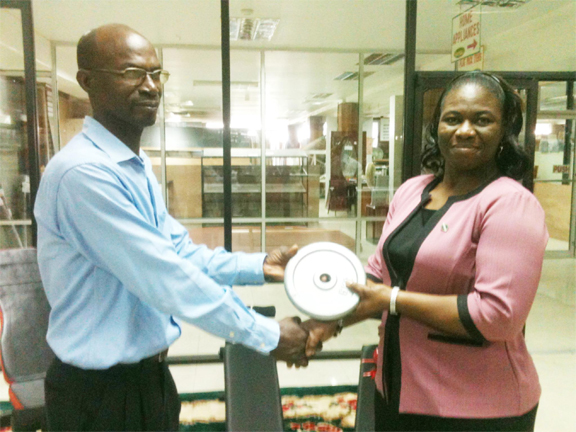 Lyndon France, head of the Technical Department of Buxton United receives a gym plate from Shonell Yarde, Manager of the Gym and Home Appliances Department as a symbolic gesture of the donation yesterday morning at the Gafsons Industries Limited, Huston.