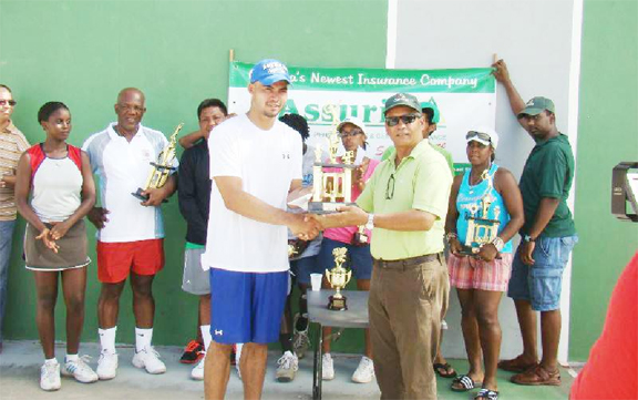Men's singles champion Anthony Downes collects his trophy from Assuria's Dick Wesenhager as other contestants look on.