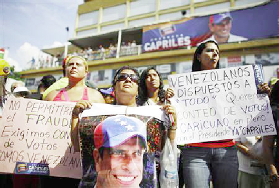 Supporters of opposition leader Henrique Capriles demonstrate in front of Capriles's campaign headquarters with signs that read, ''Venezuelans ready for anything. We want a vote recount'' (R) and ''We won't allow fraud,'' in Caracas, April 15, 2013. (Reuters/Tomas Bravo)