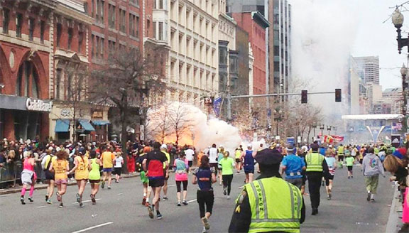 Runners continue to run towards the finish line of the Boston Marathon as an explosion erupts near the finish line of the race in this photo exclusively licensed to Reuters by photographer Dan Lampariello after he took the photo in Boston, Massachusetts. REUTERS/Dan Lampariello.