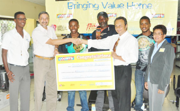 Courts Managing Director Clyde De Haas hands over the cheque to Peter Abdool, third from right. Others in picture are from left, PRO Kester Abrams, Clive Atwell, Howard Eastman, boxer Kishan Simon and Pamela Humphrey.