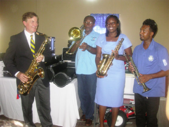 Jazz time: US Ambassador Brent Hardt (left) with Alex Foster (second from left) and Avia Lindie (third from left) as they check out the musical instruments.