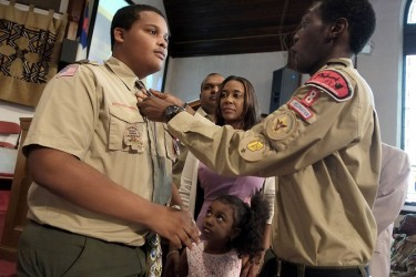 Tevin Barnes (left) receives his Eagle tie from one of his Troop mates while his family looks on. From second left are: his stepfather, Tony Persaud; mother, Wendy Cummings-Persaud and sister Tamia Lynn Persaud.  (New Jersey Star Ledger photo)