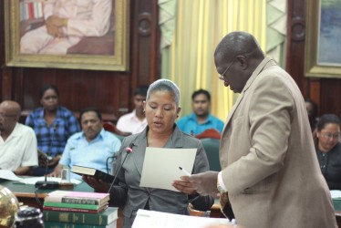Moruca resident Rennita Williams being sworn in as the APNU's new Region One Member of Parliament by Clerk of the National Assembly Sherlock Isaacs. (Arian Browne photo)