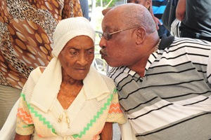 Centenarian Louise Pierre, left, receives a congratulatory kiss from her son Hercules during her 100th birthday celebrations in Blanchisseuse yesterday.(Trinidad Express photo)