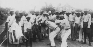 Drummer and dancers at the Baghwat Festival, Port Mourant, 1938