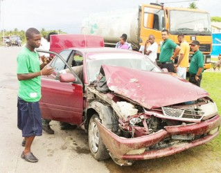 The badly damaged car with the truck in background