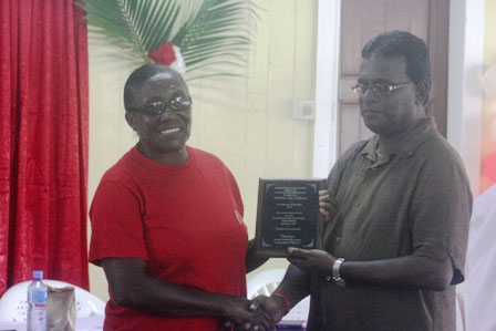 Chief Medex, Ministry of Health, Baldeo James (right) present a long-serving midwife with her award (GINA photo)