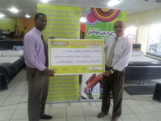 Courts donation- Marketing Manager at Courts Guyana Inc Pernell Cummings (left) handing the cheque to Chairman of the Fundraising Committee of the Guyana Hindu Dharmic Sabha Raj Singh.