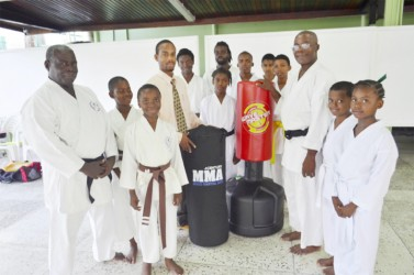 Dhillon De Mendonca (fourth left) presents the equipment to Sensei Winston Dunbar in the presence of other students and instructors.