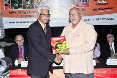 Invest Guyana Publisher Lokesh Singh (left) presents a copy of the Magazine 'Invest Guyana' to President Donald Ramotar (GINA photo)