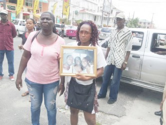 Barbara James (left), mother of the deceased, along with a relative outside the Georgetown Magistrate's Court yesterday.