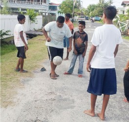 Showing them how it's done! This group of youngsters looks on as their colleague dribbles a football.