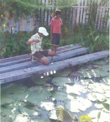 This young man looks on as his friend tries to hook a 'big' fish.