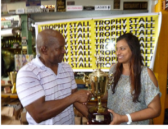 Devi Sunich, wife of Ramesh Sunich, the proprietor of the Trophy Stall hands over the Mr. Fitness Paradise winner's trophy to Donald Sinclair, owner of Fitness Paradise Gym.