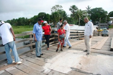 Minister in the Ministry of Local Government and Regional Development Norman Whittaker (second from left) and Minister in the Ministry of Finance Juan Edghill (right) examining the Kumaka-San Jose Bridge (GINA photo)