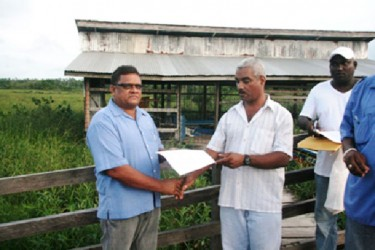 Regional Executive Officer Nigel Fisher (right)  hands over the variation order for the Kumaka-San Jose Bridge to contractor Deodat Singh (GINA photo)