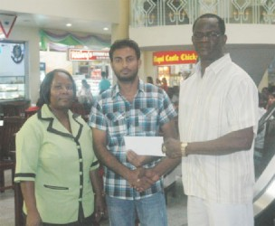 City Mall Supervisor Imran Ayube (centre) hands over the sponsorship cheque to Chairman of the Boyce & Jefford Classic Management Committee, Colin Boyce (right) inside the City Mall while a staff member looks on.