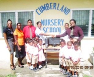 Berbice Chamber of Commerce past president Imran Sacoor (right) presents a computer system to the Cumberland Nursery School at a ceremony attended by pupils of the school and Chamber representatives.