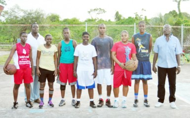 Some members of the Guyana national female basketball team  surrounded by members of the training staff.
