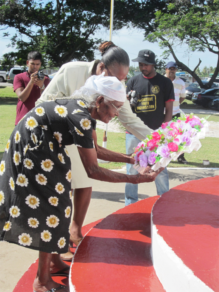 Pooran's widow, the closest surviving relative of the Enmore Martyrs, is given support as she lays a wreath under her husband's name.