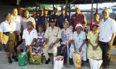 Assistant Superintendent of police, Jiaram Ramlakhan (seated, centre) and others with five of the six residents who received hampers