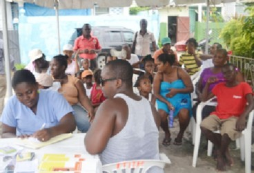 Residents of Rasville awaiting medical treatment at the medical outreach (GINA photo)