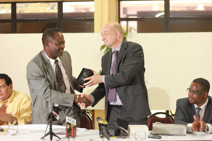 UClan's Deputy Vice Chancellor Professor Dave Phoenix (right) presents UG's Vice Chancellor Jacob Opadeyi with a symbol of the partnership their institutions share after the signing of the MOU between the two universities yesterday.