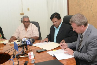 Finance Minister Dr Ashni Singh (centre) looks on as European Union Ambassador Robert Kopecky signs the Financing Agreement. Also in photo is senior Finance Ministry official Tarachand Balgobin. (GINA photo)