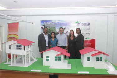 HfHG National Director Rawle Small, Praharshanie Beharry, Beharry Chairman Anand Beharry, Beharry Director Anjuli Beharry, and HfHG's Communication and Resource Development Manager Colette Hytmiah stand behind the three model homes that qualified families may choose from. The model furthest right is disability friendly. (Photo by Arian Browne)