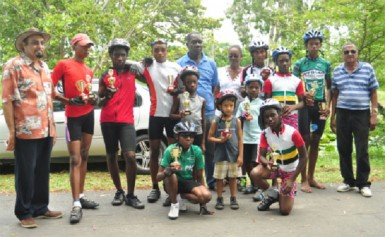 Winners and runners up pose with their trophies upon completion of yesterday's fourth annual World Olympic Day five-race BMX cycle programme. They are flanked by president of the GOA, K Juman-Yassin (extreme left), Joseph Britton, president of the GCF, Cheryl Thompson and National Cycling Coach, Hassan Mohamed. (Orlando Charles photo)