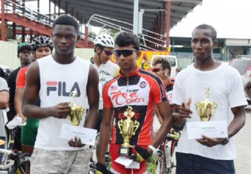 Olympic Day Triathlon winners, Daniel Scott, Raynauth Jeffery and Cavin McDonald with their trophies and prize money after the activity in the National Park.