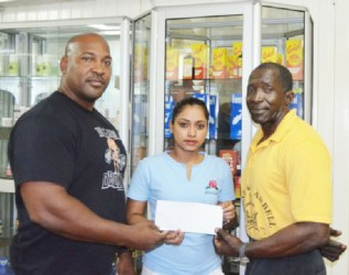 John 'Big John' Edwards (left) receiving his sponsorship cheque from Marketing Executive of NEW GPC INC., Livasti Bhooplall as his Kingsrow Barbell gym mate Winston Stoby looks on.
