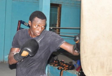 Dexter Gonsalves hitting the punching bag during one of his recent training sessions at the Forgotten Youth Foundation (FYF) Gym. (Orlando Charles photo)