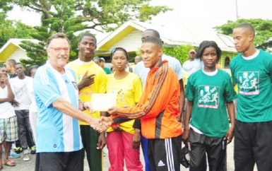 Argentina's Ambassador to Guyana Luis Alberto Martino presents an envelope to Police's A team member, Dennis Horatio in the presence of Kevin Bayley, Nathaniel Giddings, Abidemi Charles, Janelle Jonas and Jowyne Johnson.