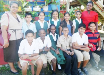 Teachers, Shamena Charran (left) and Magdalene Sobers-Williams posing with the top students of Novar Primary
