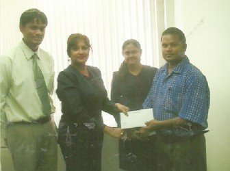 Senior Supervisor of Republic Bank Rose Hall Branch, Seema Bridemal, hands over sponsorship cheque to RHTYSC's Rohan Etwaru.
