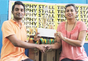 Treasurer of the GCF Ryan Singh collects the sponsorship cheque and trophies for the tournament from Devi Sunich of the Trophy Stall.