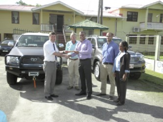 A representative of the German Development Bank (left) making the symbolic handover of the two vehicles to Natural Resources Minister, Robert Persaud.