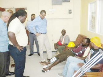 Minister of Natural Resources and the Environment, Robert Persaud (standing first from right) speaking to Fabian Anthony, a survivor of the vehicular accident.  (GINA photo)