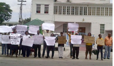 University of Guyana staffers protest in front of the Ministry of Education yesterday