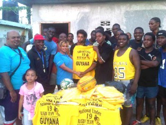 Shenny Lall, manager of the Long Hi Industries presenting a quantity of jerseys to captain of the national under-19 rugby team, Godfrey Broomes in the presence of the coaches, Laurie Adonis and Troy Yhip and other ruggers.