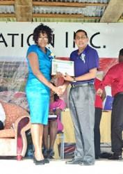 Blairmont Champion worker, Avril Patricia Spencer receives her certificate from Jairam Petam (GINA photo)