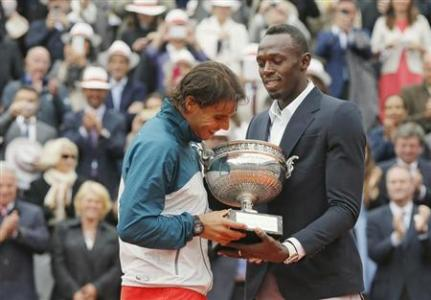 Rafael Nadal (L) of Spain receives the trophy from Jamaican sprinter Usain Bolt after defeating compatriot David Ferrer in their men's singles final match to win the French Open tennis tournament at More... Credit: REUTERS/Gonzalo Fuentes