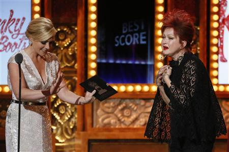 """Singer Cyndi Lauper  (right) enters the stage to accept the award for Best Original Score Written for the Theatre for """"Kinky Boots"""" at Tony Awards in New York"""